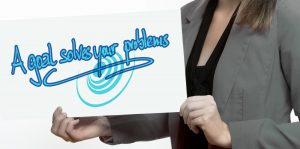 Lady holding plaque saying A Goal Solves Problems | Augmentable Marketing Limited